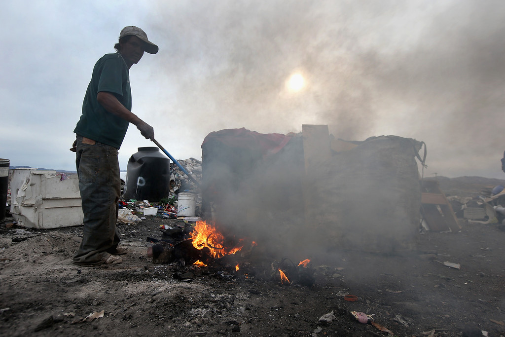 . NOGALES, MEXICO - MARCH 05:  Jorge Dareil burns the plastic off copper wiring he scavenged at the Tirabichi garbage dump on March 5, 2013 in Nogales, Mexico. About 30 families, including Carlos, live at the landfill, searching for recyclables to sell for a living. They have received aid from the non-profit Home of Hope and Peace, which plans to expand it\' assistance to the dump\'s impoverished populace in the future.  (Photo by John Moore/Getty Images)