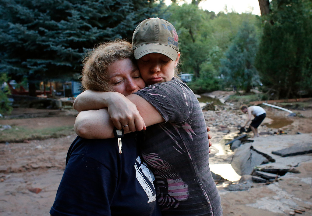 . Local residents Holly Rob, right, and her neighbor and friend Pam Bowers hug after a day salvaging Rob\'s belongings after floods destroyed Rob\'s home, in Lyons, Colo., Friday Sept. 13, 2013. Days of heavy rains and flash floods which washed out the town\'s bridges and destroyed the electrical and sanitation infrastructure have left many Lyons residents cut off with minimal access to help, and sectioned off the town into several pieces not reachable one to the other. (AP Photo/Brennan Linsley)