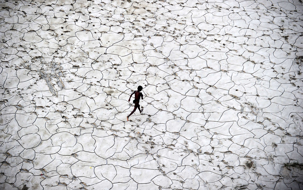 . An Indian street child plays in a dry river bed after flood waters receded in Allahabad on October 25, 2013.  Sanjay Kanojia/AFP/Getty Images