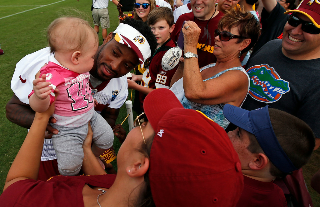 . Washington Redskins receiver Santana Moss holds a little fan for a picture after practice at the team\'s NFL football training facility, Sunday, July 27, 2014, in Richmond, Va. (AP Photo/Alex Brandon)