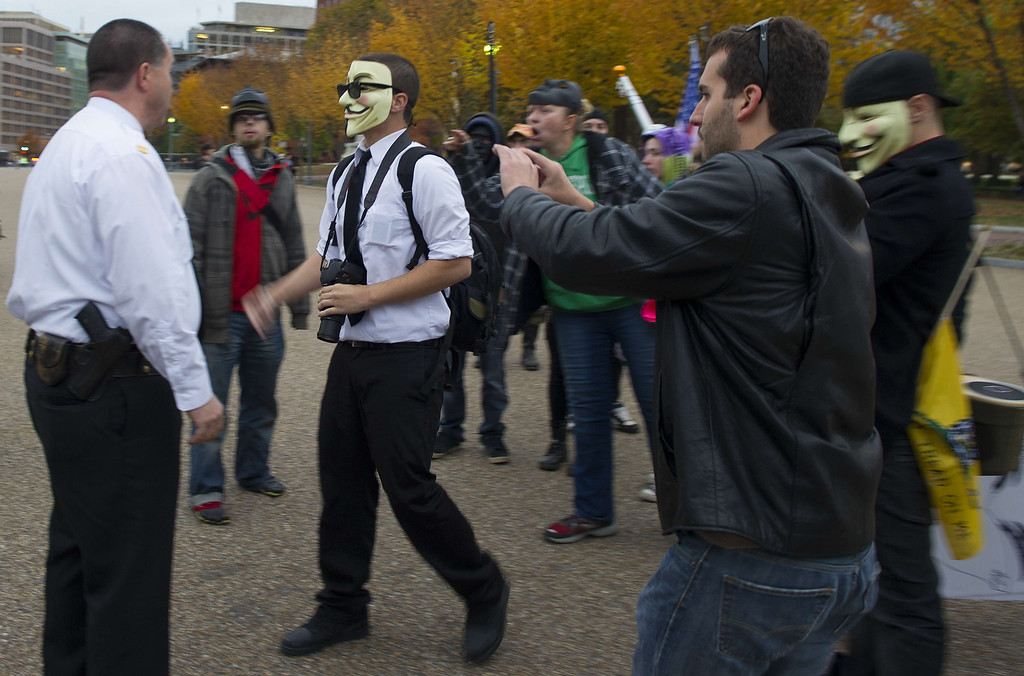 . Demonstrators, and supporters of the group Anonymous, argue with Uniformed Secret Service officers during a protest against corrupt governments and corporations in front of the White House in Washington, DC, November 5, 2013, as part of a Million Mask March of similar rallies around the world on Guy Fawkes Day.       AFP PHOTO / Jim WATSON/AFP/Getty Images