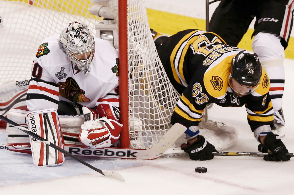 . Chicago Blackhawks goalie Corey Crawford (L) and Boston Bruins\' Brad Marchand battle for the puck during the second period in Game 6 of their NHL Stanley Cup Finals hockey series in Boston, Massachusetts, June 24, 2013. REUTERS/Winslow Townson
