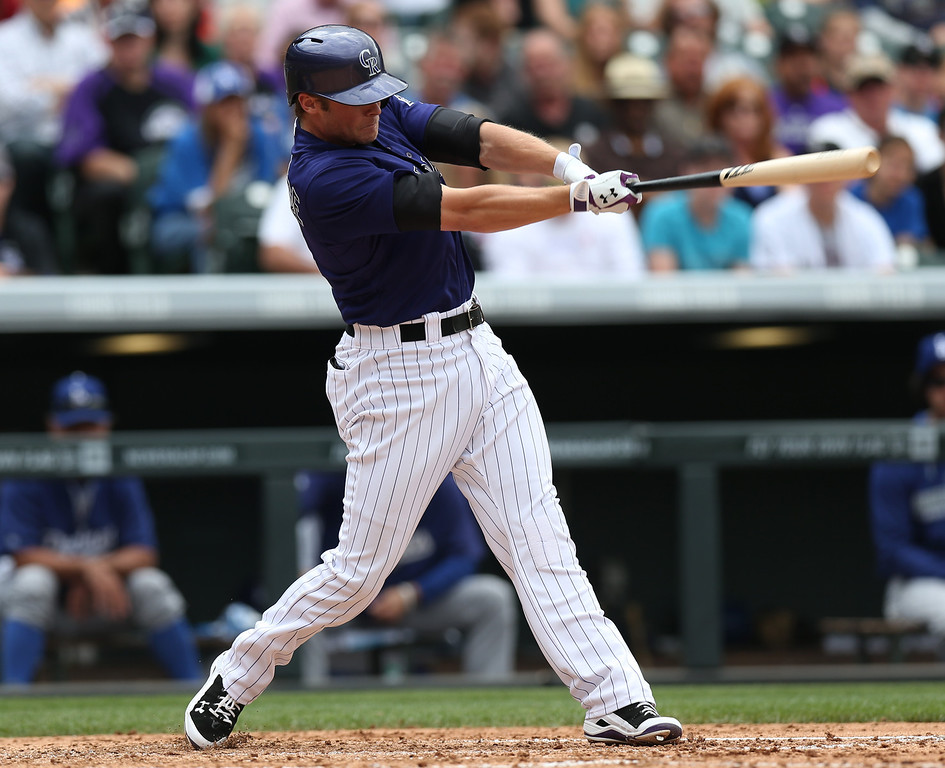 . Colorado Rockies\' Josh Rutledge follows the flight of his RBI-single against the Los Angeles Dodgers in the fifth inning of a baseball game in Denver on Saturday, June 7, 2014. (AP Photo/David Zalubowski)