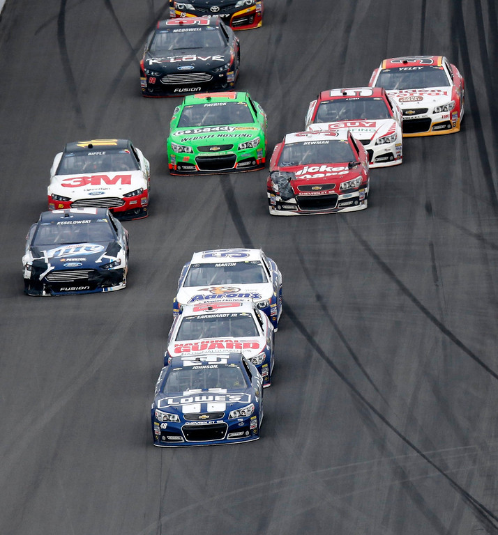 . NASCAR driver Jimmie Johnson (bottom) brings his No. 48 Chevrolet to the finish line in first place ahead of Dale Earnhardt Jr. and the rest of the field during the NASCAR Sprint Cup Series Daytona 500 race at the Daytona International Speedway in Daytona Beach, Florida February 24, 2013. REUTERS/Pierre Ducharme (UNITED STATES - Tags: SPORT MOTORSPORT)