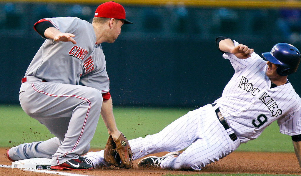 . Cincinnati Reds\' Todd Frazier, left, tags out Colorado Rockies\' DJ LeMahieu, right, as he tries to steal third during the first inning of a baseball game, Friday, Aug. 30, 2013, in Denver. (AP Photo/Barry Gutierrez)