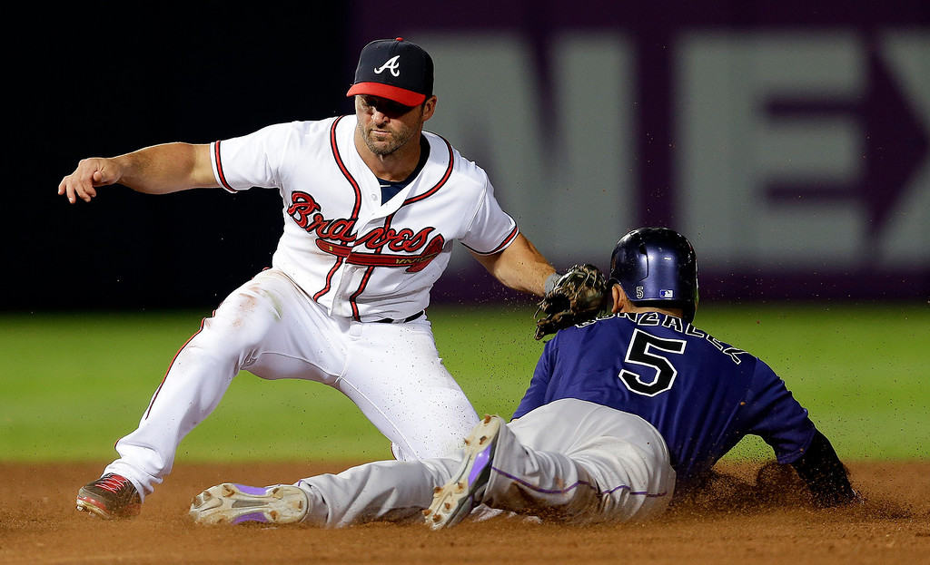 . Colorado Rockies\' Carlos Gonzalez, right,  is tagged out by Atlanta Braves second baseman Dan Uggla, left, as he attempts to steal second base in the seventh inning of a baseball game in Atlanta, Monday  July 29, 2013. (AP Photo/John Bazemore)