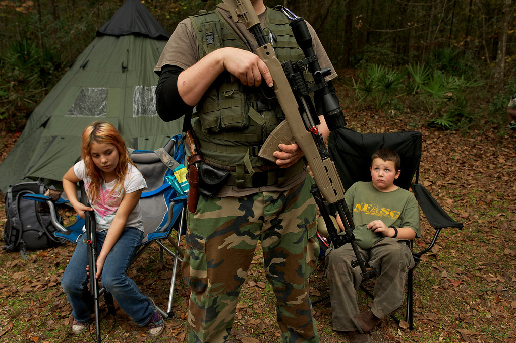 """. Members of the North Florida Survival Group wait with their rifles before heading out to perform enemy contact drills during a field training exercise in Old Town, Florida, December 8, 2012. The group trains children and adults alike to handle weapons and survive in the wild. The group passionately supports the right of U.S. citizens to bear arms and its website states that it aims to teach \""""patriots to survive in order to protect and defend our Constitution against all enemy threats\"""".   REUTERS/Brian Blanco"""