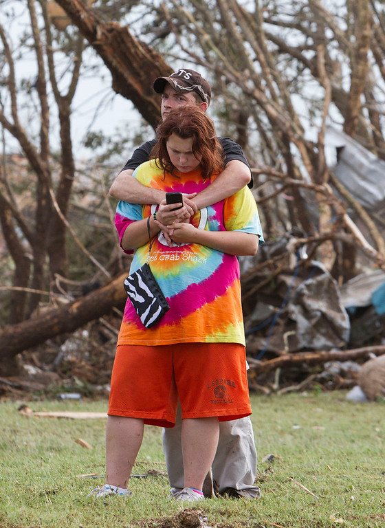 . A couple after a tornado moves through Moore, Okla. on Monday, May 20, 2013. (AP Photo/Alonzo Adams)
