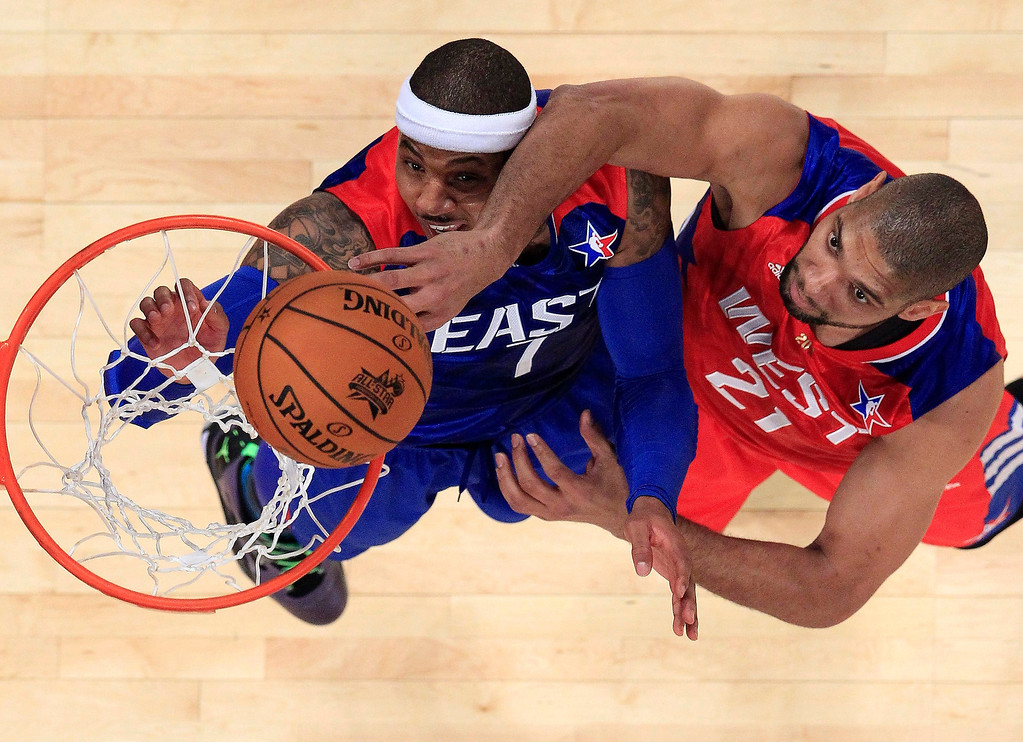 . West Team\'s Tim Duncan of the San Antonio Spurs (21) shoots over East Team\'s Carmelo Anthony (7) of the New York Knicks, during the first half of the NBA All-Star basketball game Sunday, Feb. 17, 2013, in Houston. (AP Photo/Lucy Nicholson, Pool)