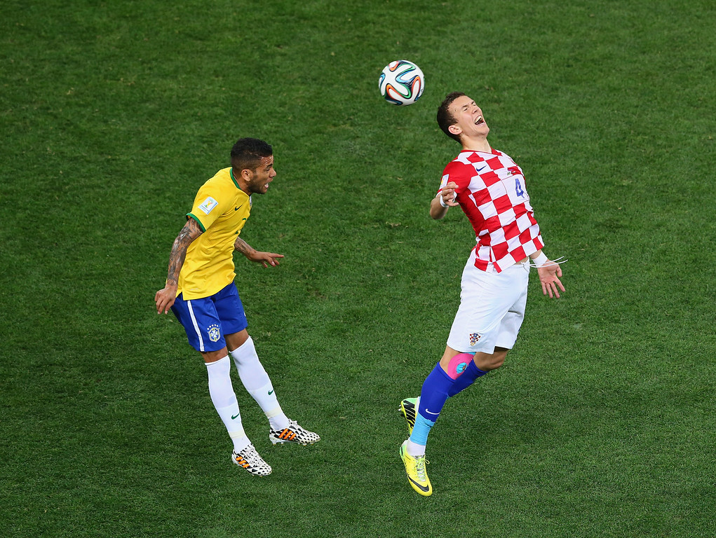 . van Perisic of Croatia goes up for a header against Dani Alves of Brazil during the 2014 FIFA World Cup Brazil Group A match between Brazil and Croatia at Arena de Sao Paulo on June 12, 2014 in Sao Paulo, Brazil.  (Photo by Kevin Cox/Getty Images)