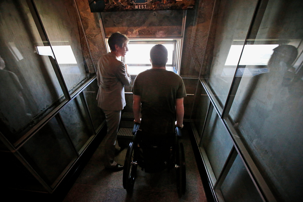 . Interior Secretary Sally Jewell, left, talks with Marine Cpl. Mark Fidler, from Reading, Pa., who was wounded in Afghanistan, inside the Washington Monument in Washington, Monday, May 12, 2014, during a ceremony to celebrate its re-opening.  (AP Photo)