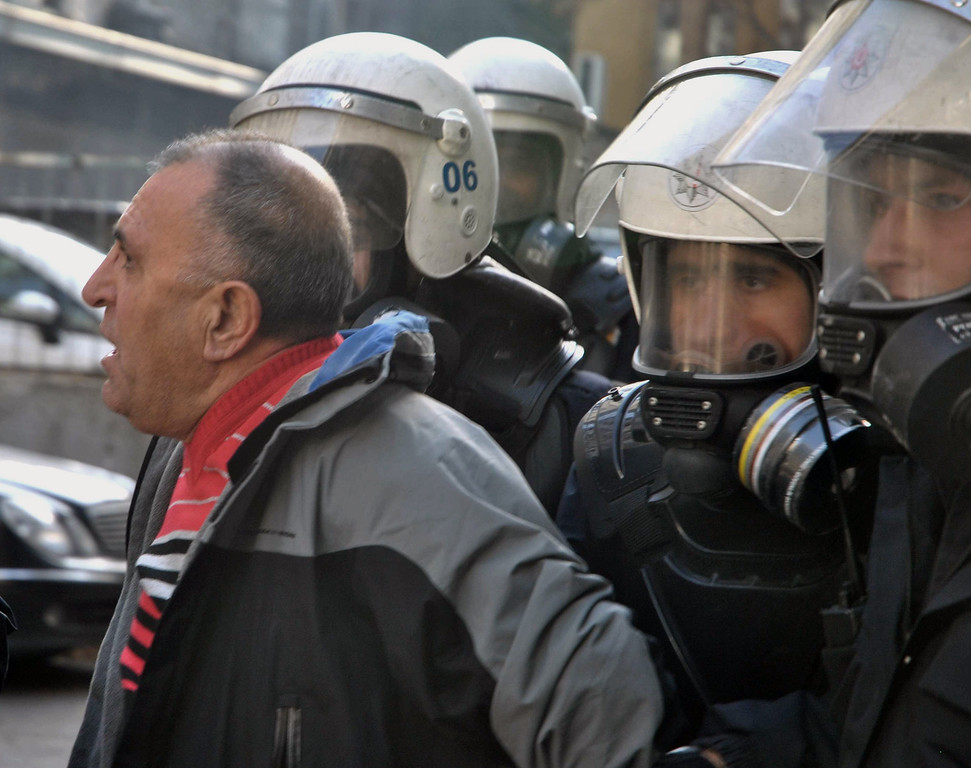 . Riot police detain a man as they use water cannons and pepper gas to disperse thousands of Turkish teachers who were gathered to protest against the government\'s education and economic policies in Ankara, Turkey, Saturday, Nov. 23, 2013.(AP Photo)