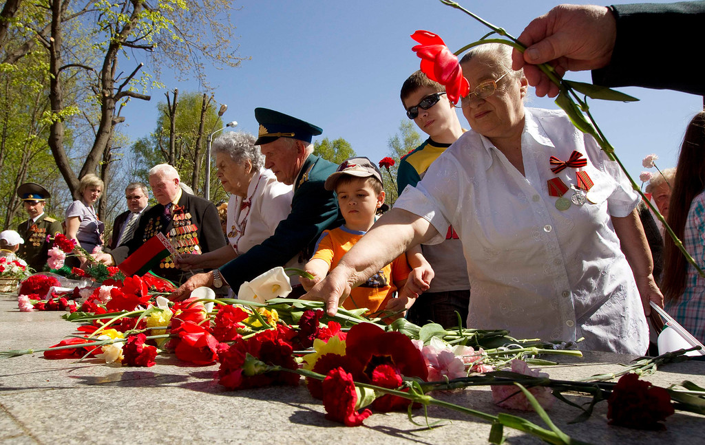 . People lay flowers at a monument during Victory Day celebrations in the town of Molodechno, some 60 km (37 miles) northwest of Minsk May 9, 2013. Belarus commemorates the 68th anniversary of the Soviet Union\'s victory over Nazi Germany on May 9.  REUTERS/Vasily Fedosenko