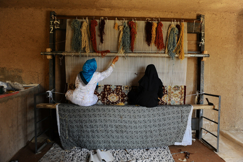 . In this picture taken on June 26, 2014, Afghan workers weave a carpet at a traditional factory in Herat.  AFP PHOTO/Aref Karimi/AFP/Getty Images
