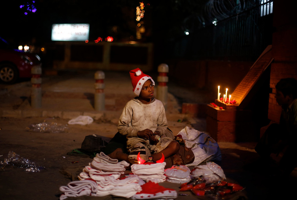 . A young Indian boy sells Christmas merchandise outside the Sacred Heartís Cathedral in New Delhi, India, Tuesday, Dec. 24, 2013. Though Hindus and Muslims comprise the majority of the population in India, Christmas is celebrated with much fanfare. (AP Photo/Altaf Qadri)