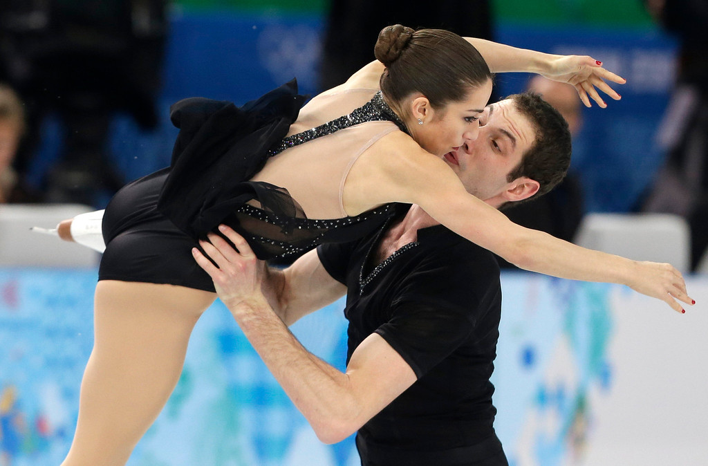 Description of . Marissa Castelli and Simon Shnapir of the United States compete in the pairs short program figure skating competition at the Iceberg Skating Palace during the 2014 Winter Olympics, Tuesday, Feb. 11, 2014, in Sochi, Russia. (AP Photo/Darron Cummings)