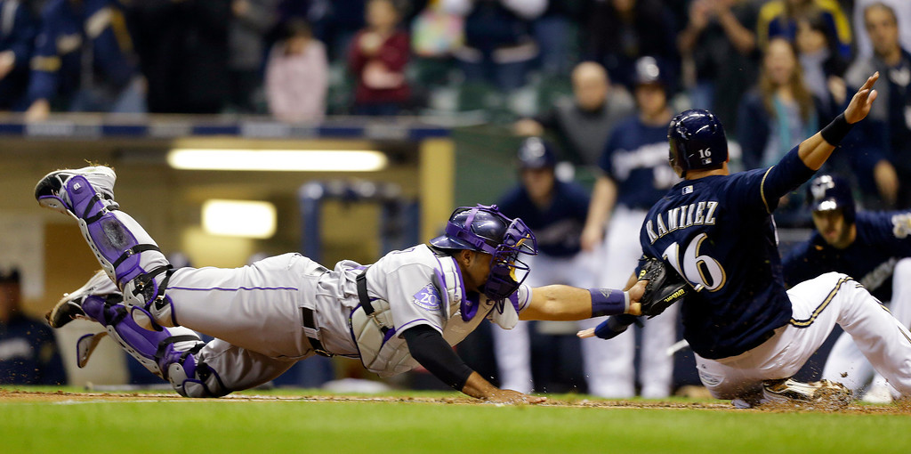 . Colorado Rockies catcher Wilin Rosario, left, dives to tag out Milwaukee Brewers\' Aramis Ramirez(16) at home plate during the third inning of a baseball game, Wednesday, April 3, 2013, in Milwaukee. (AP Photo/Jeffrey Phelps)