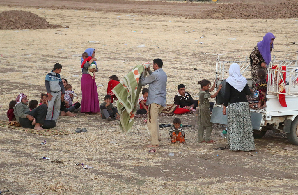 . Displaced Iraqis from the Yazidi community settle outside the camp of Bajid Kandala at Feeshkhabour town near the Syria-Iraq border, in Iraq Saturday, Aug. 9, 2014.  (AP Photo/ Khalid Mohammed)