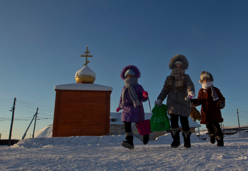 . Children run across the central square in the village of Tomtor in the Oymyakon valley in northeast Russia, January 28, 2013. The coldest temperatures in the northern hemisphere  since the beginning of the 20th century have been recorded in the Oymyakon valley, known as the \'Pole of Cold\', where according to the United Kingdom Met Office a temperature of -67.8 degrees Celsius (-90 degrees Fahrenheit) was registered in 1933.     REUTERS/Maxim Shemetov