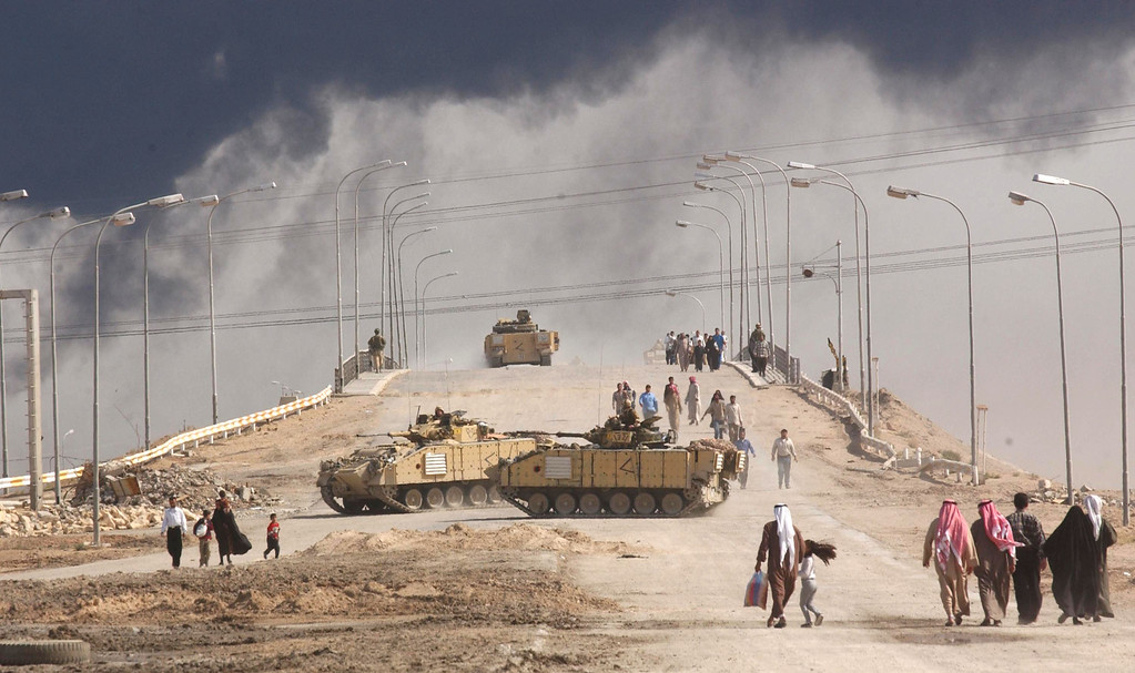 . Civilians on foot pass tanks on a bridge near the entrance to the besieged city of Basra March 29, 2003 in Iraq. (Photo by Spencer Platt/Getty Images)