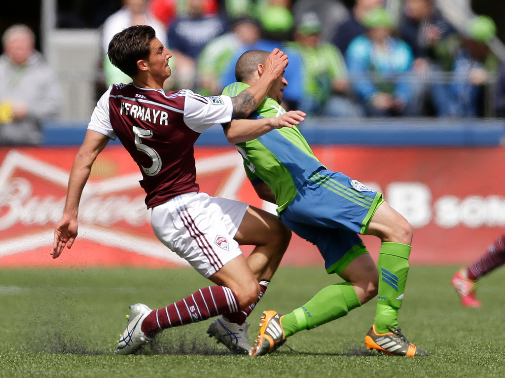 . Seattle Sounders\' Osvaldo Alonso, right is fouled by Colorado Rapids\' Thomas Piermayr, left, Saturday, April 26, 2014, in the first half of an MLS soccer match in Seattle. Piermayr was given a yellow card on the play. (AP Photo/Ted S. Warren)