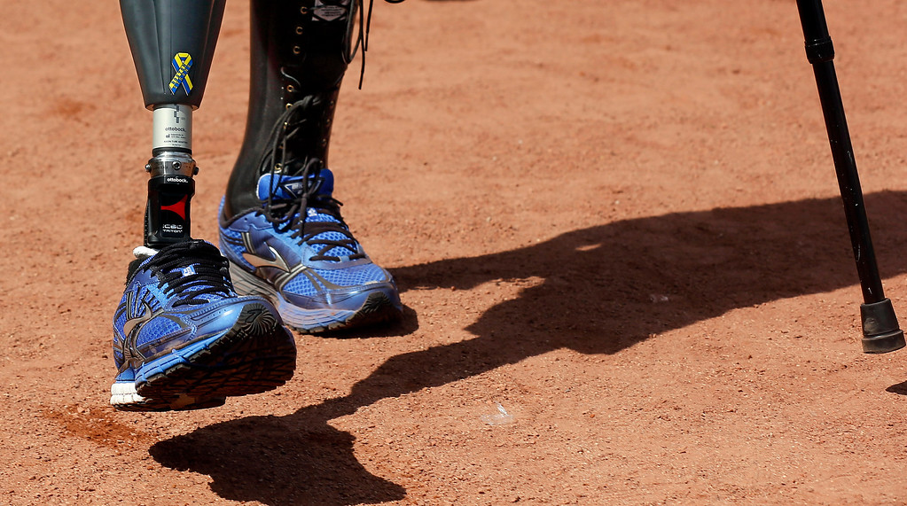 """. A \""""Boston Strong\"""" sticker is seen on the prosthetic leg of Boston Marathon bombing survivor Marc Fucarile after he threw out the ceremonial first pitch before the baseball game between the Boston Red Sox and the Baltimore Orioles at Fenway Park in Boston Monday, April 21, 2014. (AP Photo/Winslow Townson)"""
