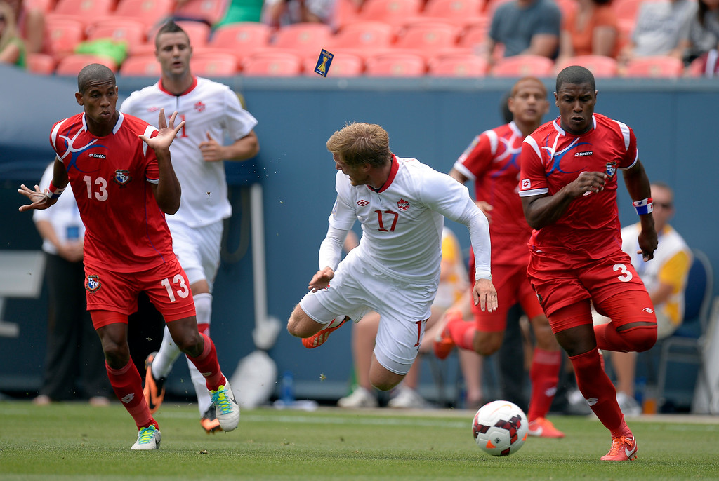 . Marcel De Jong #17 of Canada gets tripped up by Jean Carlos Cedeno #13 during the first half of the CONCACAF Gold Cup soccer game July 14, 2013 at Sports Authority Field at Mile High. Cedeno was given a yellow card on the play. (Photo By John Leyba/The Denver Post)