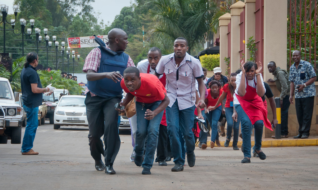 . Civilians who had been hiding inside during gunbattles manage to flee from the Westgate Mall in Nairobi, Kenya Saturday, Sept. 21, 2013. (AP Photo/Jonathan Kalan)