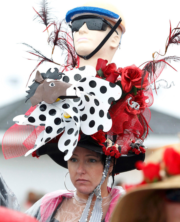 . A spectator has her elaborate hat getting wet in the rain as she awaits the running of the 139th Kentucky Derby horse race at Churchill Downs in Louisville, Kentucky May 4, 2013. REUTERS/Matt Sullivan