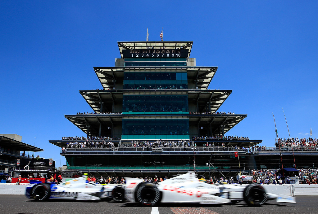 . Simon Pagenaud, driver of the #77 LucasOil Honda races ahead of JR Hildebrand, driver of the #21 Preferred Freezer/Ed Carpenter Racing Chevrolet, as they pass the pagoda during the 98th running of the Indianapolis 500 Mile Race at Indianapolis Motorspeedway on May 25, 2014 in Indianapolis, Indiana.  (Photo by Jamie Squire/Getty Images)