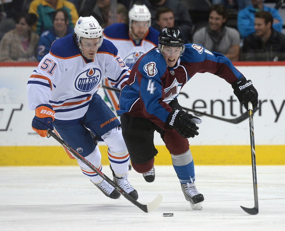 . DENVER, CO. - DECEMBER 19: Edmonton center Anton Lander (51) and Colorado defenseman Tyson Barrie (4) skated after the puck in the third period. The Colorado Avalanche defeated the Edmonton Oilers 4-2 Thursday night, December 19, 2013.  Photo By Karl Gehring/The Denver Post