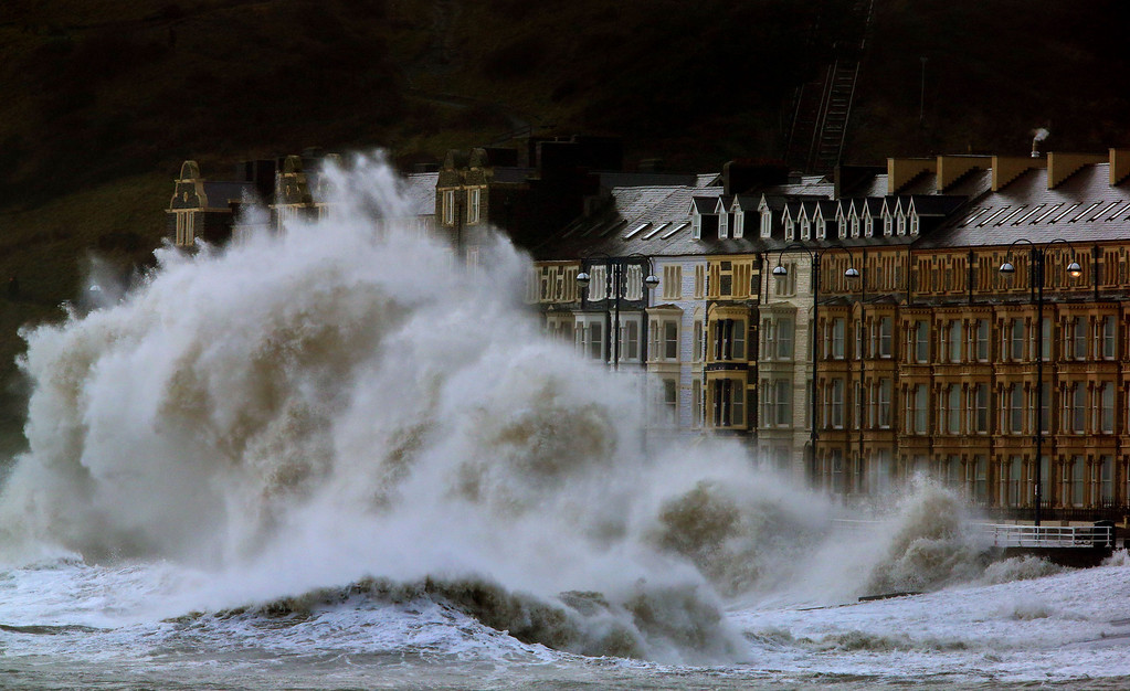 . Waves crash against the Aberystwyth coastline, in Wales,  as strong winds and high tides continue to blow in from the west,  Monday Jan.  6, 2014. Residents along Britain\'s coasts are braced for more flooding as strong winds, rain and high tides lash the country. At least three people have died in a wave of stormy weather that has battered Britain since last week, including a man killed when his mobility scooter fell into a river in Oxford, southern England. (AP Photo/PA, Dave Thompson)