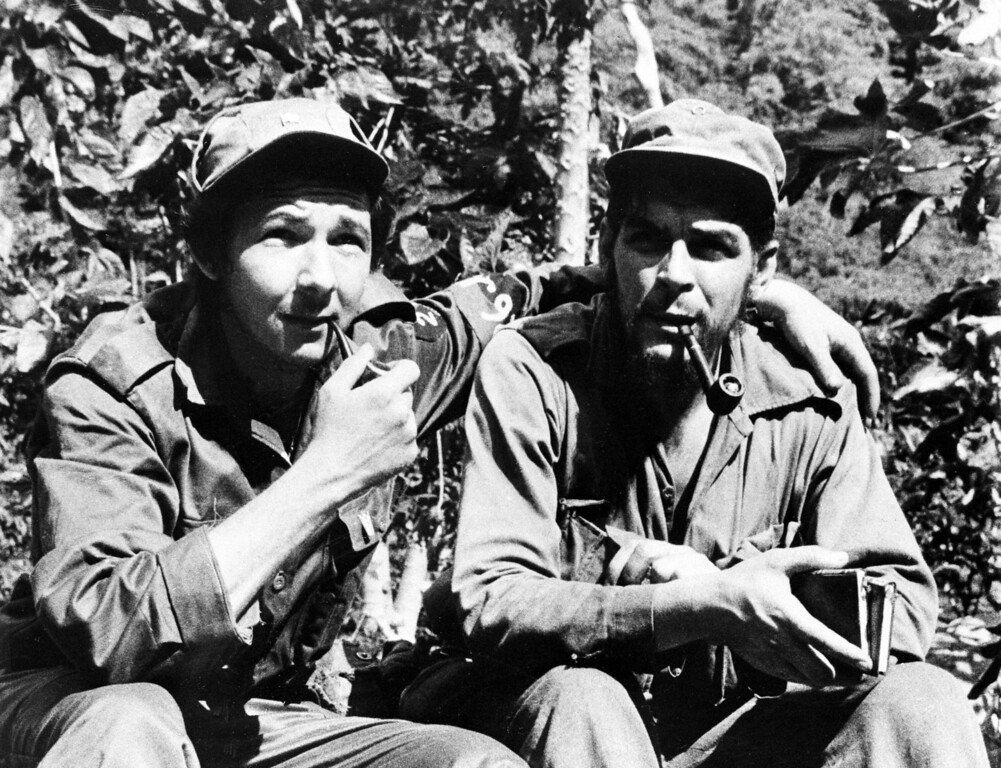 """. Raul Castro, left, younger brother to Cuban leader Fidel Castro, has his arm around second-in-command, Ernesto \""""Che\"""" Guevara, Argentine national, in their Sierra de Cristal mountain stronghold south of Havana, Cuba, during the Cuban revolution in June 26, 1958.  (AP Photo/Andrew St. George)"""