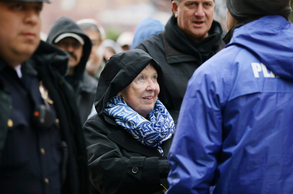 . Lillian Lawson, 80 enters through security before a ceremony to mark the 50th anniversary of the assassination of John F. Kennedy, Friday, Nov. 22, 2013, at Dealey Plaza in Dallas.  (AP Photo/Tony Gutierrez)
