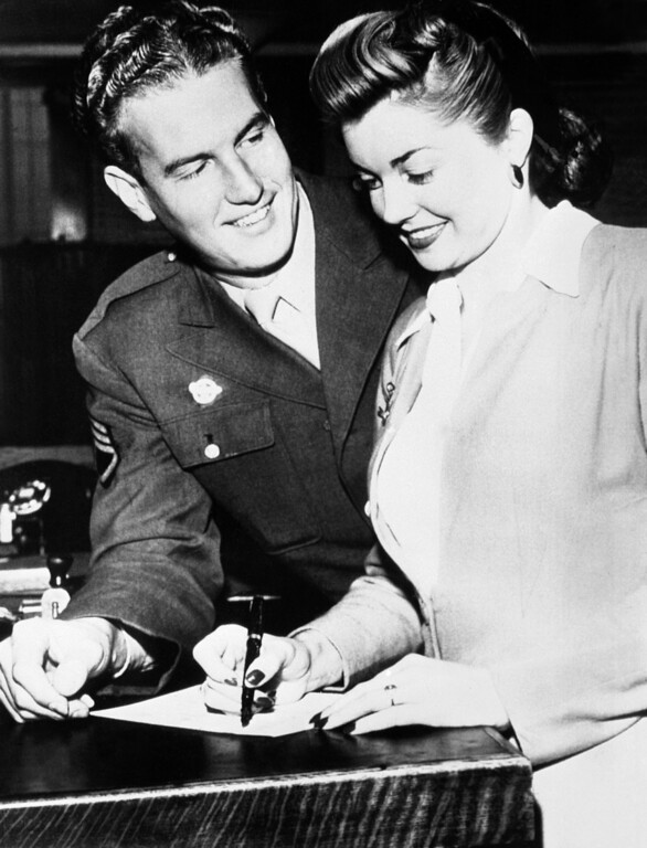. Esther Williams, famous American swimmer who became a star of the film world, was married to Staff Sergeant Ben Gage, formerly radio announcer in the Bob Hope program, at Berverly Hills, Ca. on Nov. 25, 1945.  Esther Williams, signs a marriage application form at Los Angeles, California while Ben Gage watches. (AP Photo)