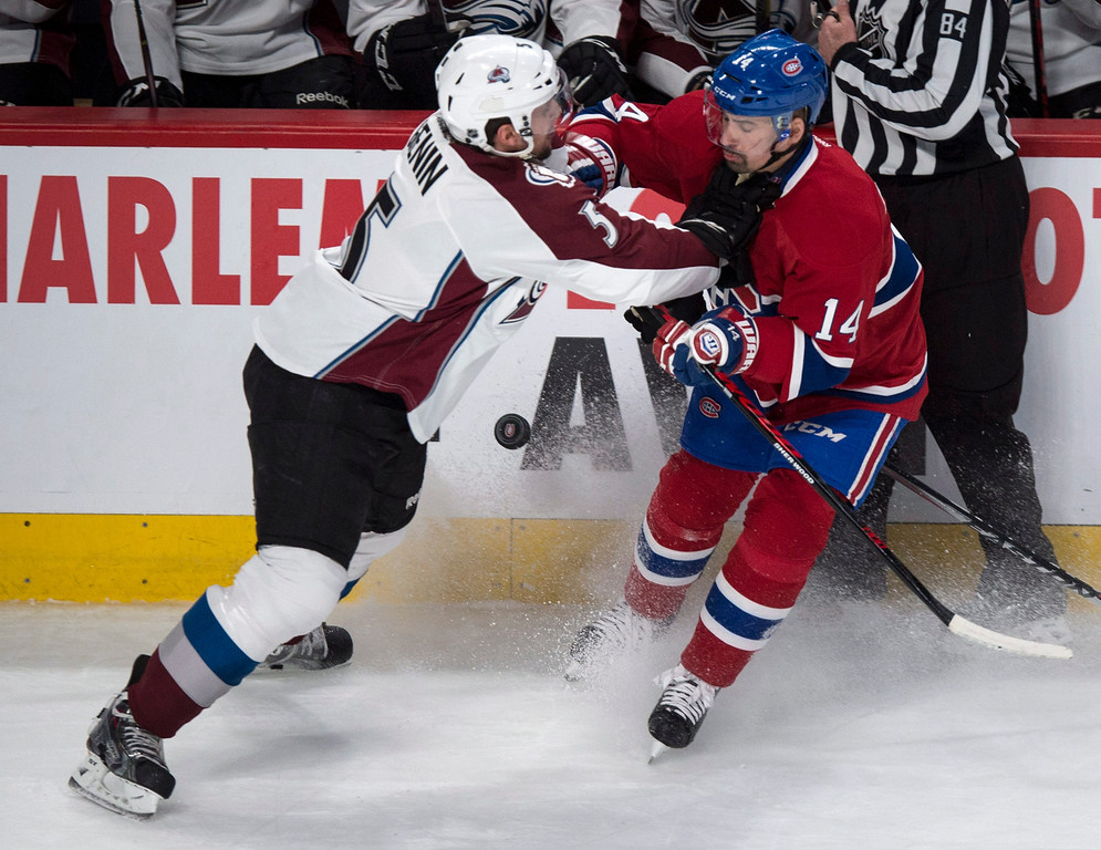 . Montreal Canadiens\' Tomas Plekanec is stopped by Colorado Avalanche\'s Nate Guenin during first period NHL hockey action Tuesday, March 18, 2014 in Montreal.  (AP Photo/The Canadian Press, Paul Chiasson)