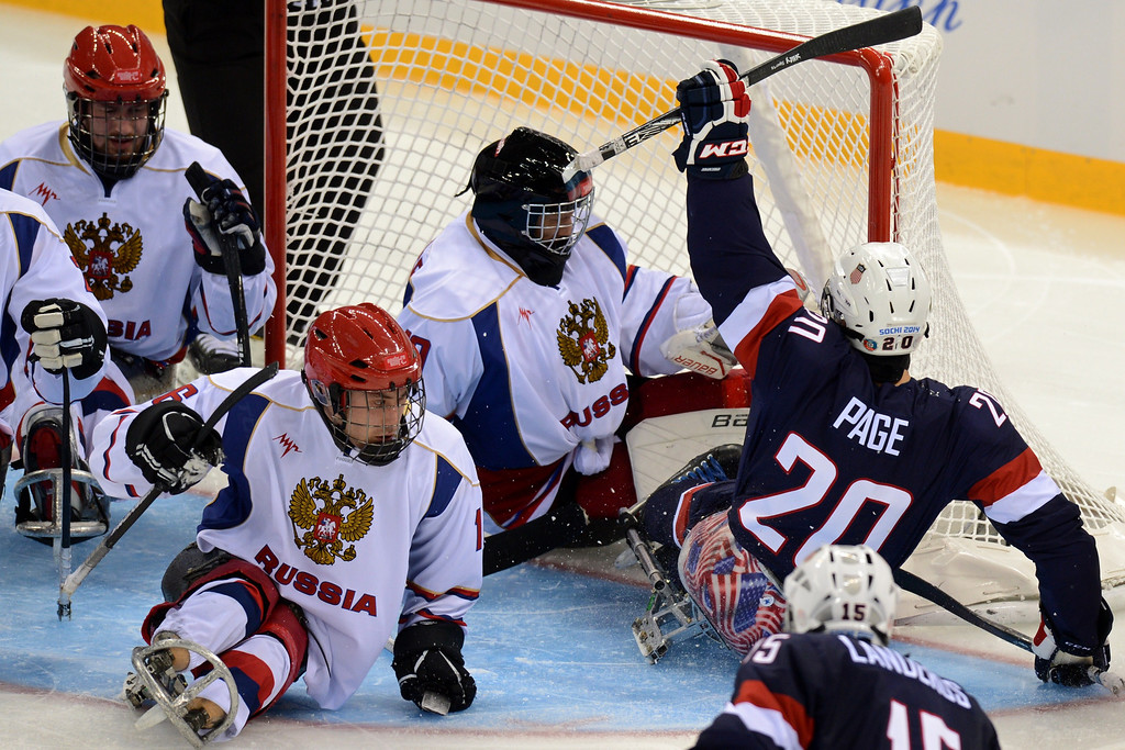 . US Adam Page (R) celebrates after scoring a goal during the ice sledge hockey match Russia vs USA during the XI Paralympic Olympic games at the Shayba stadium, near Sochi on March 11, 2014. AFP PHOTO / KIRILL KUDRYAVTSEV
