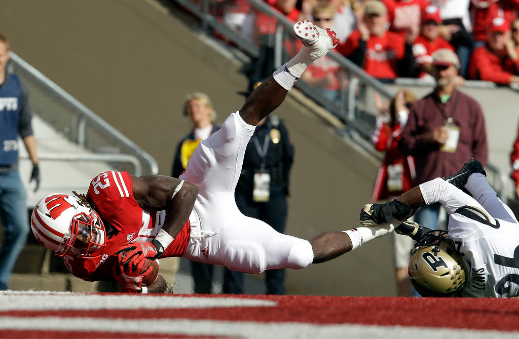 . Wisconsin\'s Melvin Gordon (25) breaks away from Purdue\'s Antoine Lewis for a touchdown run during the first half of an NCAA college football game Saturday, Sept. 21, 2013, in Madison, Wis. (AP Photo/Morry Gash)