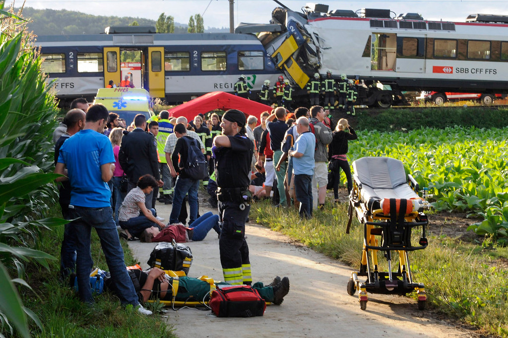 . Injured passengers are helped at the site where two passenger trains collided head-on in Granges-pres-Marnand, western Switzerland, Monday, July 29, 2013. Police say at least 44 people were injured, four of them seriously. (AP Photo/Keystone, Laurent Gillieron)