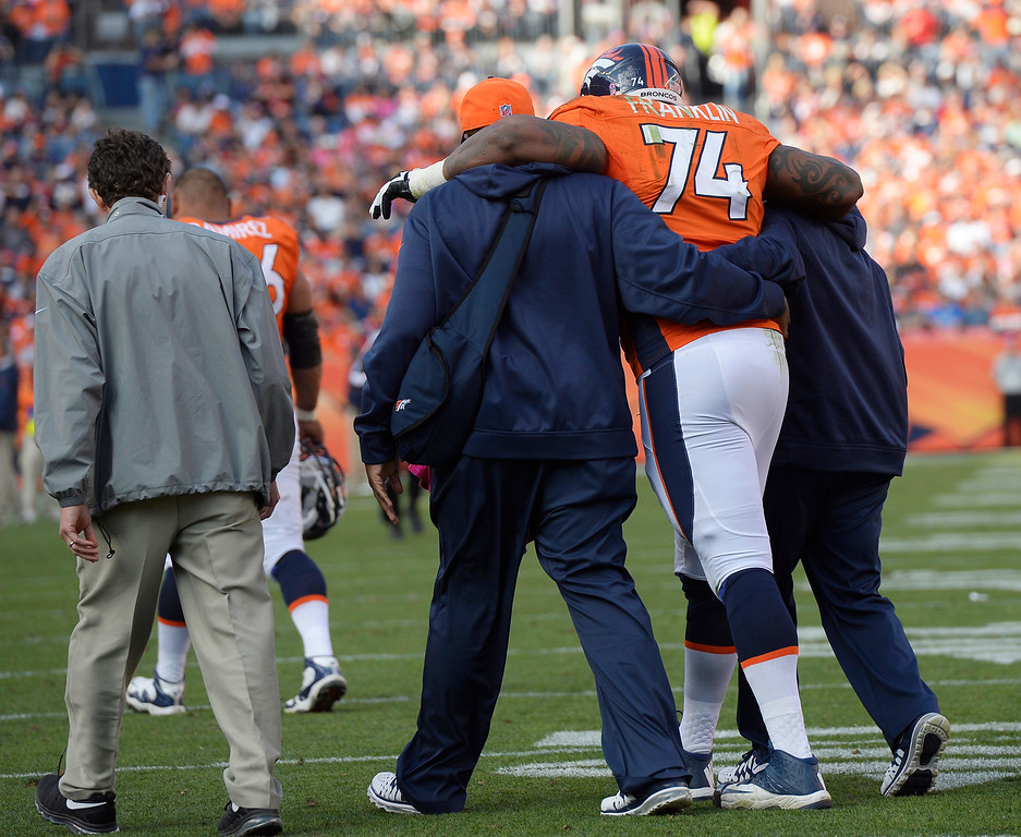 . Denver Broncos tackle Orlando Franklin (74) is helped off the field after being injured in the third quarter. The Denver Broncos take on the Jacksonville Jaguars at Sports Authority Field at Mile High in Denver on October 13, 2013. (Photo by Joe Amon/The Denver Post)