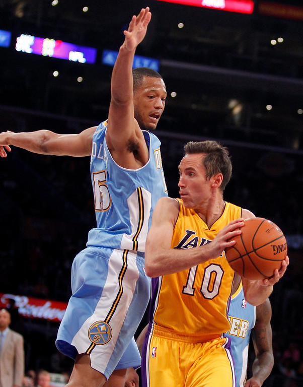 . Los Angeles Lakers guard Steve Nash (10) looks to make a pass with Denver Nuggets forward Anthony Randolph defending during an NBA preseason basketball game Sunday, Oct. 6, 2013 in Los Angeles. (AP Photo/Alex Gallardo)