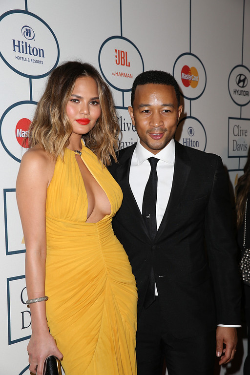 . Recording artist John Legend (R) and model Chrissy Teigen arrive at the 2014 HYUNDAI / GRAMMYs Clive Davis Pre-GRAMMY Gala Activation + Equus Fleet Arrivals at The Beverly Hilton Hotel on January 25, 2014 in Beverly Hills, California.  (Photo by Chelsea Lauren/Getty Images for Hyundai)