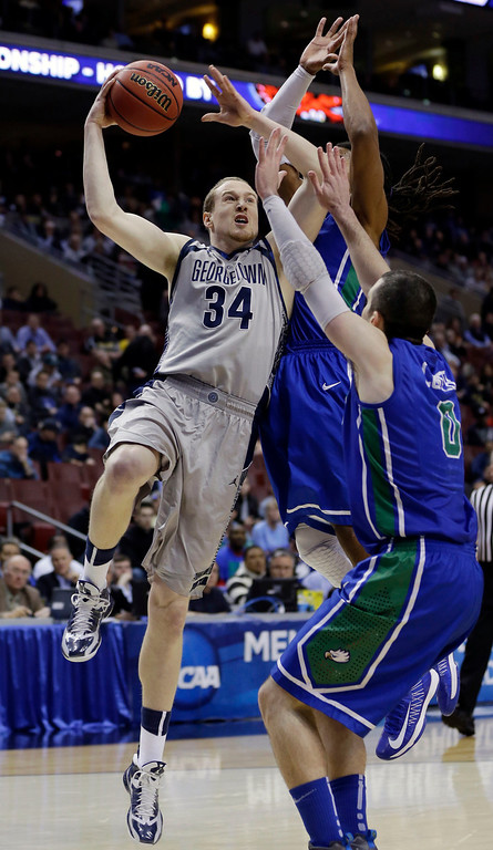 . Georgetown\'s Nate Lubick, left, shoots against Florida Gulf Coast\'s Brett Comer, right, and Sherwood Brown during the first half of a second-round game of the NCAA college basketball tournament on Friday, March 22, 2013, in Philadelphia. (AP Photo/Matt Rourke)