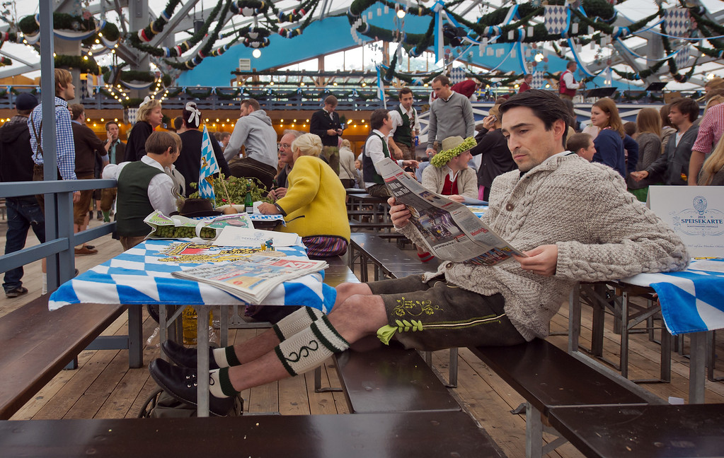 """. A Visitor in bavarian style clothes reads a newspaper after he has entered the \""""Schottenhamel\"""" beer tent as fast as possible to reserve places for friends for the official launch of the Oktoberfest 2013 beer festival at Theresienwiese on September 21, 2013 in Munich, Germany. Munichs mayor Christian Ude will launch the Oktoberfest at 12.00 o\'clock in the Schottenhamel-tent by tapping the first barrel of beer with the traditional \""""O\'zapft is!\"""" (\""""It\'s tapped!\""""). The Munich Oktoberfest, which this year will run from September 21 through October 6, is the world\'s largest beer fest and draws millions of visitors. (Photo by Joerg Koch/Getty Images)"""