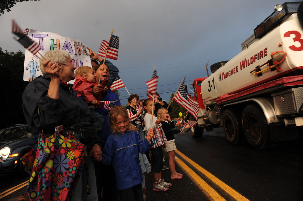 . Jan Starkweather, left, and her granddaughter Sojie Hinkle, 5, wave American flags for firefighters as they head up Fontanero street on their way back to fire camp on July 3rd, 2012. Residents of the Colorado Springs community turn out each night at the intersections of Fontanero and 31st streets in downtown Colorado Springs to show their appreciation for the firefighters coming off the fire line. Helen H. Richardson, The Denver Post