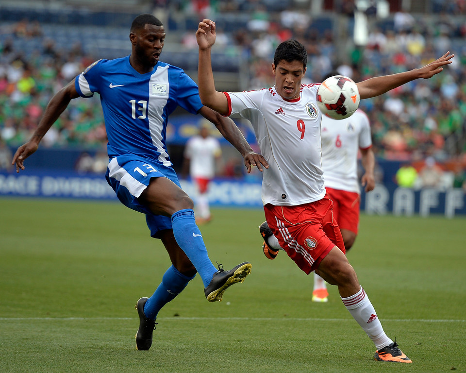 . Olvier Thomert #13 of Martinique gets bac on defense to kick the ball away from Raul Jimenez #9, of Mexico during the first half of the CONCACAF Gold Cup soccer game July 14, 2013 at Sports Authority Field at Mile High. (Photo By John Leyba/The Denver Post)