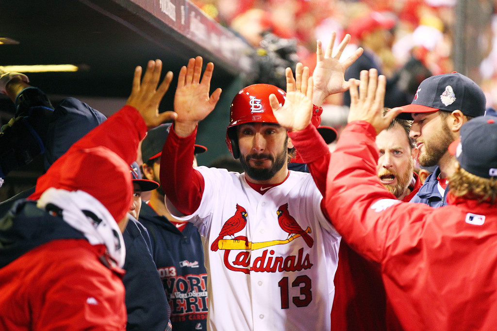 . Matt Carpenter #13 of the St. Louis Cardinals celebrates with his teammates in the dugout after scoring a run off of Carlos Beltran #3 singled to center field in the third inning against Clay Buchholz #11 of the Boston Red Sox during Game Four of the 2013 World Series at Busch Stadium on October 27, 2013 in St Louis, Missouri.  (Photo by Dilip Vishwanat/Getty Images)