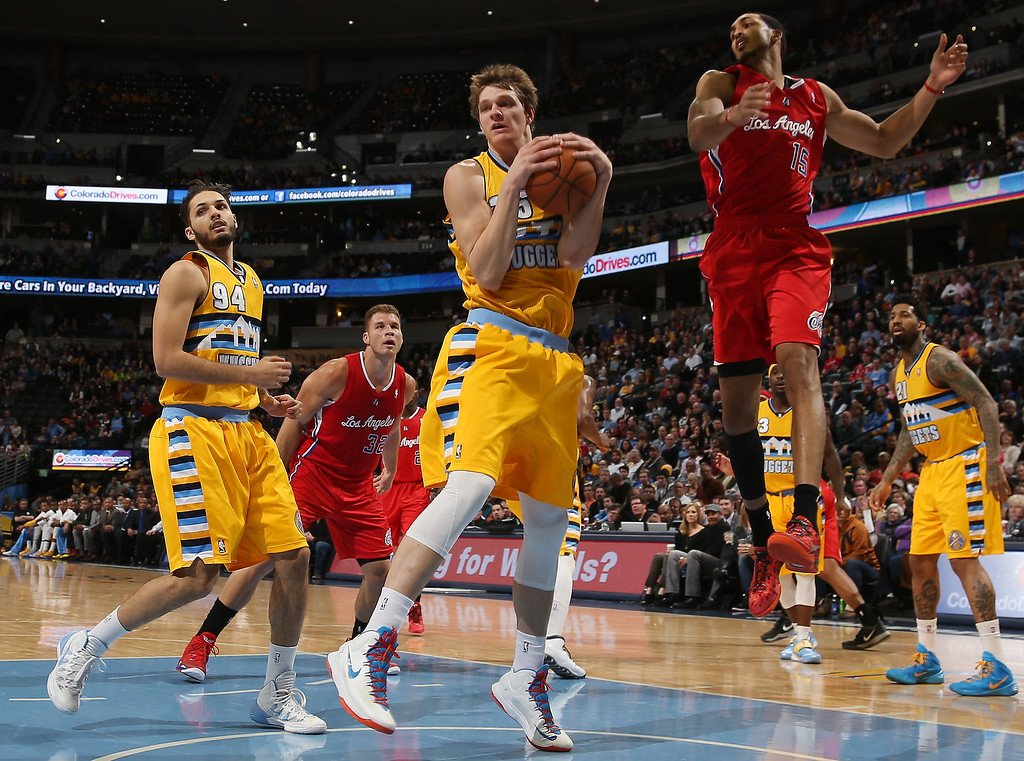 . Denver Nuggets center Timofey Mozgov, center, pulls down a rebound in front of Los Angeles Clippers forward Ryan Hollins in the first quarter of an NBA basketball game in Denver, Monday, Feb. 3, 2014. Looking on from left are Nuggets guard Evan Fournier, Clippers forward Blake Griffin and Nuggets forward Wilson Chandler. (AP Photo/David Zalubowski)