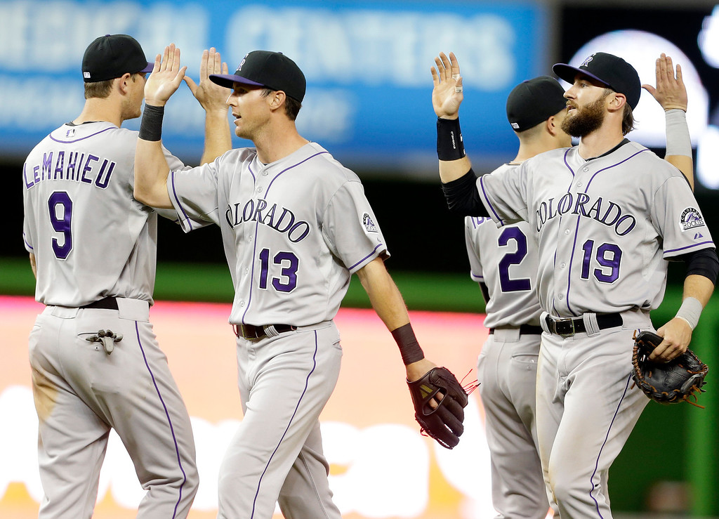 . Colorado Rockies DJ LeMahieu (9), Drew Stubbs (13) and Charlie Blackmon (19) celebrate after they defeated the Miami Marlins 6-5 in a baseball game on Wednesday, April 2, 2014, in Miami. (AP Photo/Lynne Sladky)