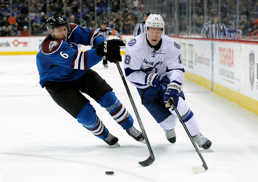 . Colorado Avalanche defenseman Erik Johnson, left, and Tampa Bay Lightning left wing Ondrej Palat, right, of the Czech Republic, fight for the puck in the second period of an NHL hockey game, Sunday, March 2, 2014 in Denver.  (AP Photo/Chris Schneider)
